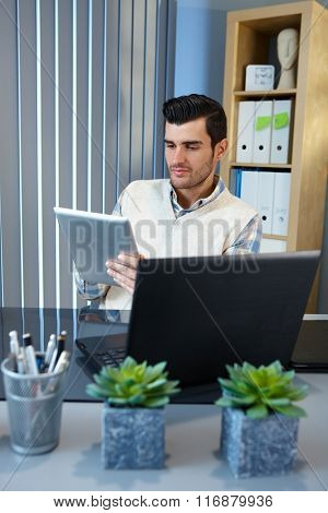 Young businessman using tablet computer, sitting at desk.
