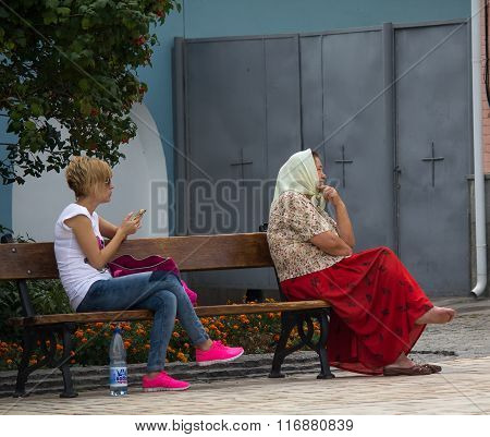Kiev, Ukraine - September 04, 2015: Two Women Of Different Ages Are Sitting On A Bench In The Courty