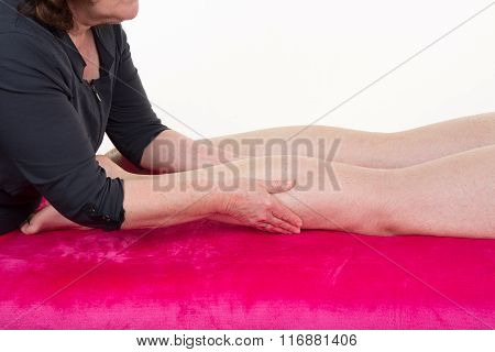 Physio Therapist Giving A Leg Massage Over White Background