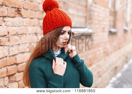 Young Beautiful Woman In A Knit Sweater On The Background Of A Brick Wall
