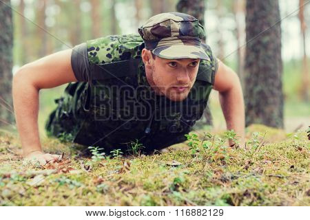 young soldier or ranger doing push-ups in forest