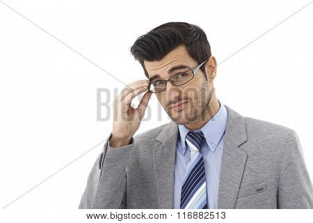 Closeup portrait of handsome young businessman in glasses, looking at camera.
