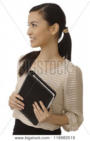 Attractive Asian businesswoman holding personal organizer, looking right, smiling happy.