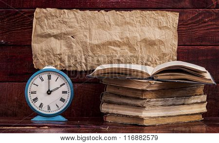 Retro alarm clock and books with wood board background