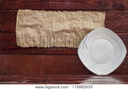 Empty plate on wooden table and old blank paper