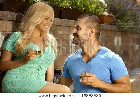 Romantic young couple with drinks in the garden, glasses of whiskey, looking at each other, smiling.