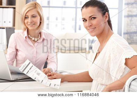 Happy smiling, brunette casual businesswoman working at office with business report in hand, looking at camera.