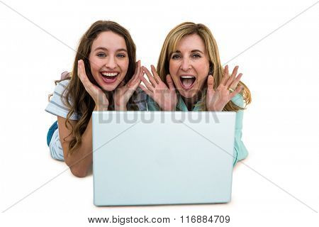 Mother and daughter watch computer lying on the ground