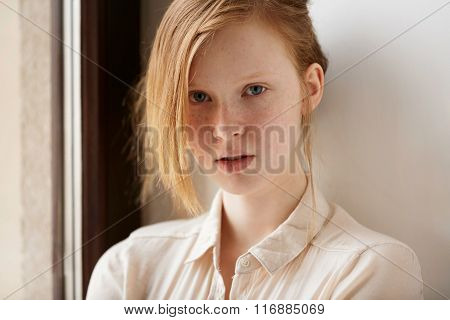 Beautiful Red-haired Girl Face. Closeup Portrait Of Cute Red Haired And Freckled Young Woman At Home