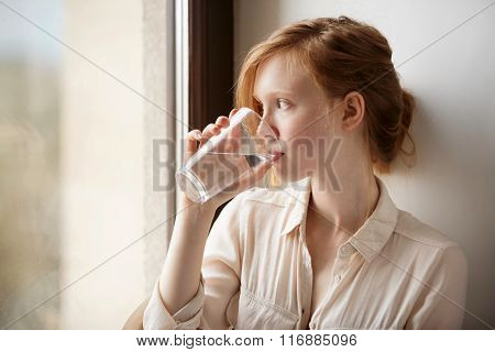 Girl Drinking Water Sitting On A Window At Home. Close-up Of Young Scandinavian Teenager Model Drink