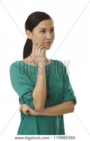 Portrait of young Asian woman turning left, standing arms crossed.