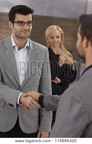 Businessmen shaking hands, smiling.