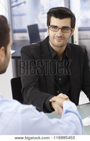 Businessmen sitting at desk, shaking hands, smiling.