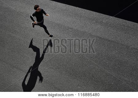 Top View Athlete Runner Training At Road In Black Sportswear At Central Position. Man Running On Cou