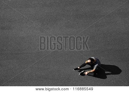 Tired Young Runner Leaning Over To Catch His Breath. Jogger Asphalt After Running And Training Exerc