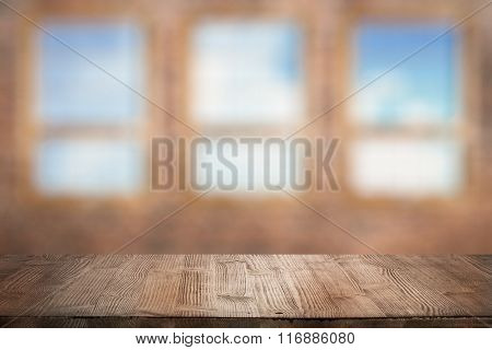 vintage wooden table in old room with big windows