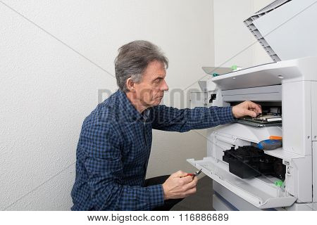 Technician Fixing Is Broken Photocopier Machine At Work