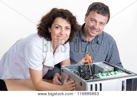 Portrait Of A Woman Fixing A Computer With A Colleague