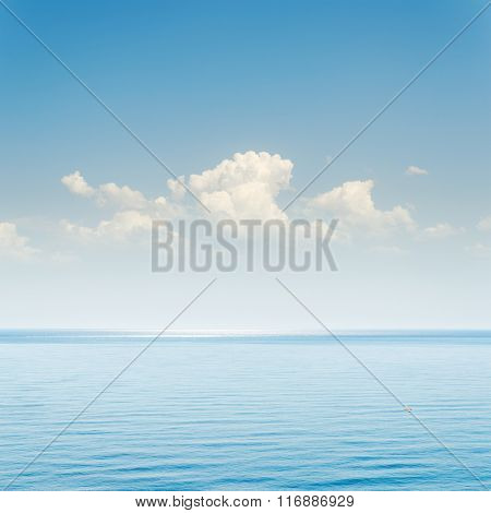 blue sea and sky with clouds over it