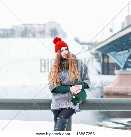 Young Beautiful Girl In A Fur Coat And A Knitted Cap Sits On A Background Of The Bridge On A Winter