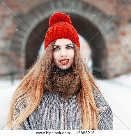 Young Beautiful Woman In A Red Hat And Coat With Fur On A Winter Day