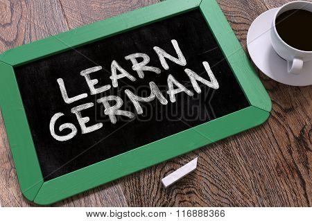 Hand Drawn Learn German Concept on Chalkboard.