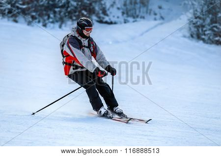 Skier in ski suit slides down from snow slope
