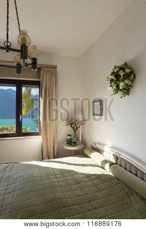 Interior of house, double bed in bedroom with classic decor