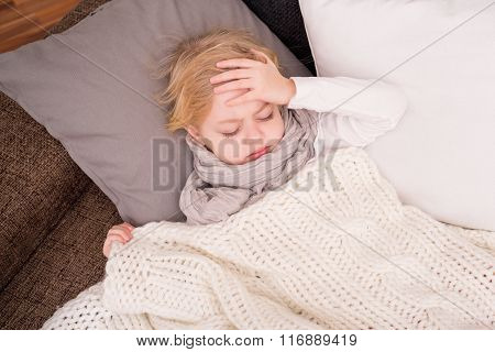 Little sick child lying on couch