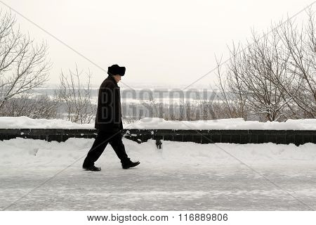 Man Walking In Winter Snow In Park