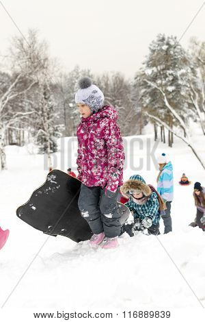 Children Sliding On Snow Slides In Russian Winter