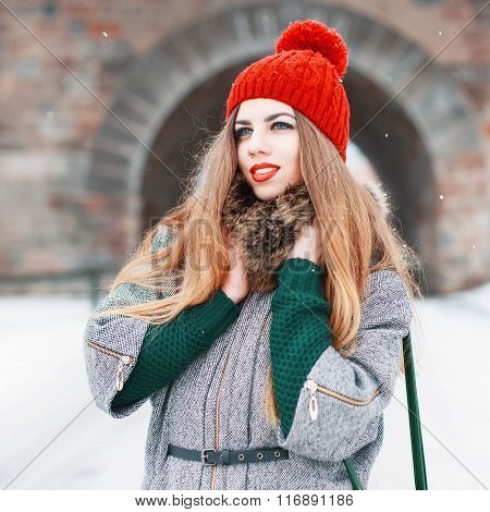 Young Pretty European Woman In Red Knitted Hat And Stylish Winter Coat On A Background Of A Stone Ar