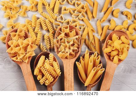 Different types of pasta lying in wooden spoons