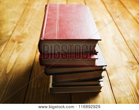 Stack of books on wooden shelf