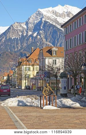 BAD RAGAZ SWITZERLAND - JANUARY 5 2015: Monument of Sitting Man and Mountains. Bad Ragaz is a city in the St. Gallen in Switzerland over Graubunden Alps. Spa and recreation is at the Tamina valley