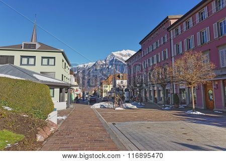 BAD RAGAZ SWITZERLAND - JANUARY 5 2015: Monument of Sitting Man and Alps Mountains. Bad Ragaz is a city in St. Gallen in Switzerland over Graubunden Alps. Spa and recreation is at the Tamina valley