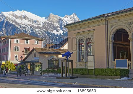 BAD RAGAZ SWITZERLAND - JANUARY 5 2015: Mountains and Spa house with Cat statue. Bad Ragaz is a city in St. Gallen in Switzerland over Graubunden Alps. Spa and recreation is in the Tamina valley