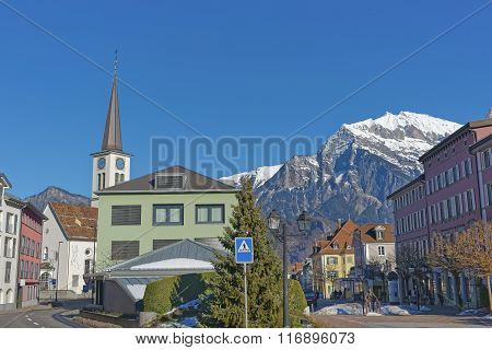 Catholic Church and Mountain in Bad Ragaz. Bad Ragaz is a city in canton St. Gallen in Switzerland. It lies over Graubunden Alps. Spa and recreation village is at end of Tamina valley