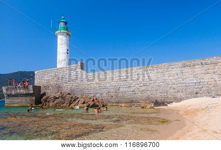Ordinary People Swimming Near White Lighthouse