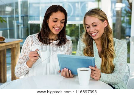 Two girls use a tablet while drinking tea