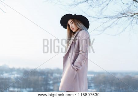 Young Beautiful Girl In Black Hat And Coat On A Background Of A Winter Landscape
