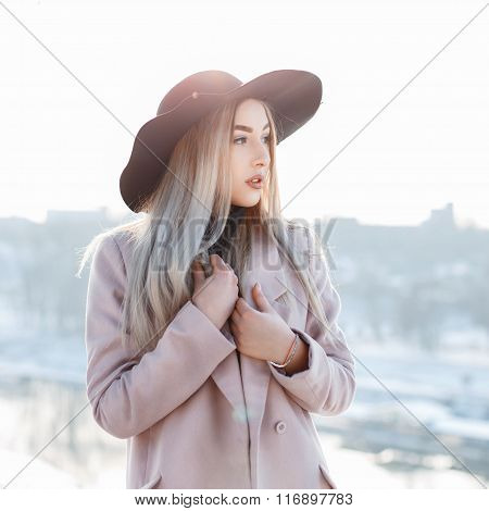 Portrait Of A Beautiful Young Girl In A Stylish Hat And Coat On A Sunny Winter Day