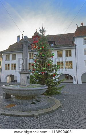 Rathaus hotel Christmas tree and Fountain in Thun Town Hall Square. Thun is a city in Swiss canton of Bern where Aare river flows out of Lake Thun. Town Hall Square is a historic center of the city