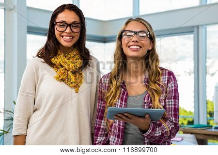 Two girls work at office on tablet