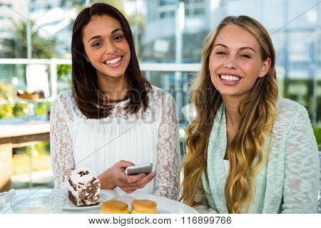 two girls watch use phone while eating