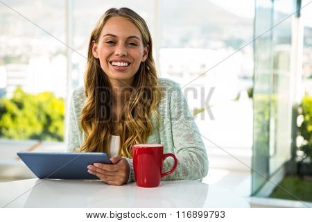 Girl with her tablet smiling at home