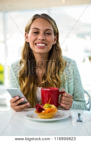 Young girl uses her phone while drinking and eating