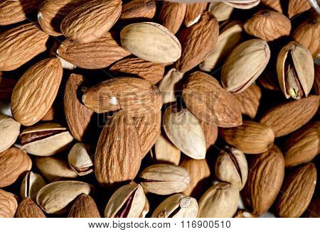 Raw vegan nuts background - almonds and pistachio