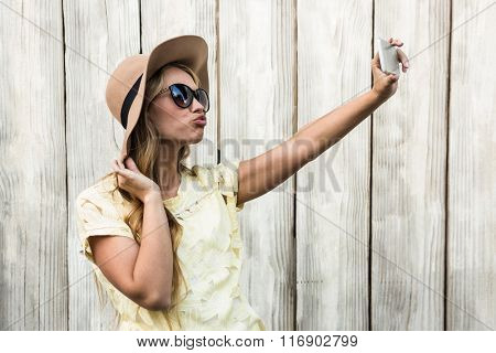 Happy woman taking a selfie with camera