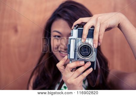 Smiling Asian woman taking photograph with camera against wooden wall